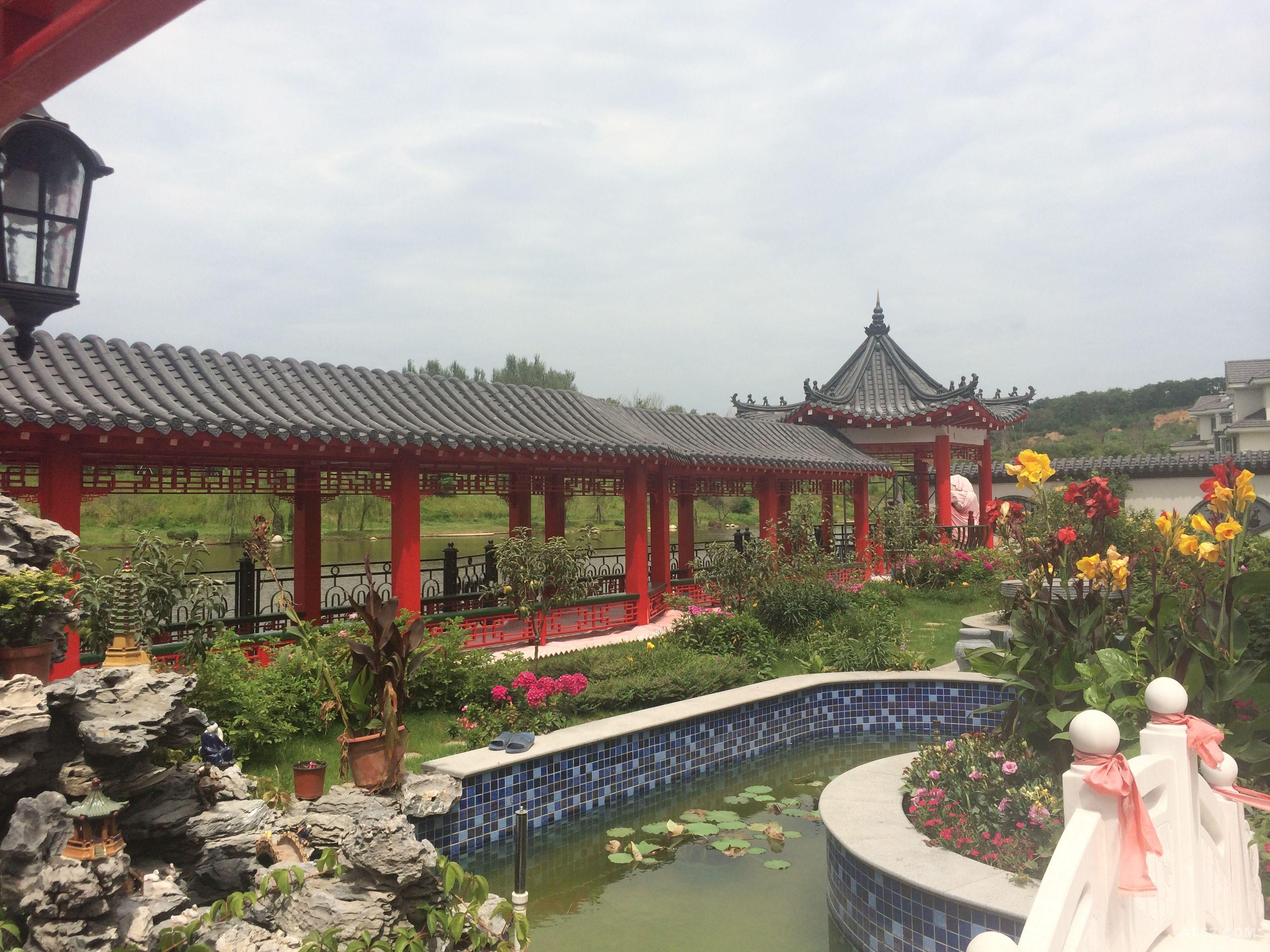 山、蓝天、花坛、古式长亭、廊桥共谱美景,仿佛天下山水都尽浓缩于后院之中。